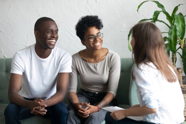 Happy African American couple at successful visit psychologist, smiling wife