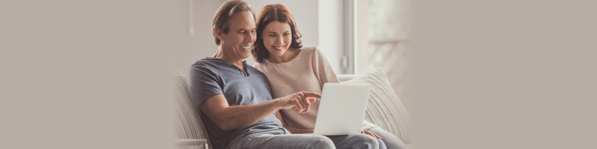 Beautiful couple is using a laptop and smiling while resting on couch at home